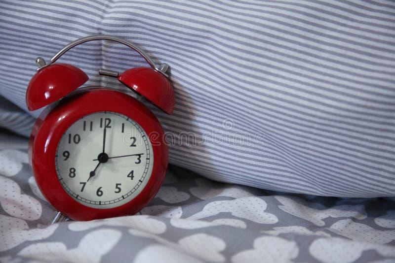 Le rétro réveil rouge se tient sur le lit photos stock