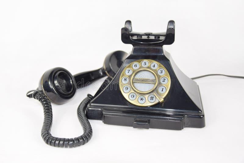 Le rétro téléphone noir, récepteur s'est étendu de côté d'isolement image libre de droits