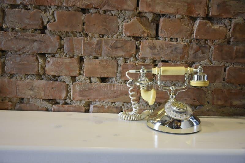 le rétro téléphone se tient sur un fond de mur de briques photo stock