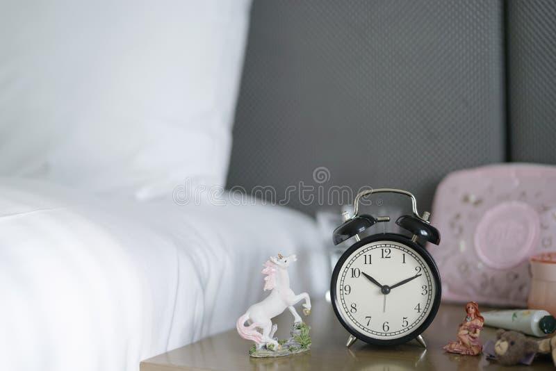 Le réveil classique sur le bureau tout près le lit avec d'autres accessoires girly aiment des miniatures de licorne et de fée, ag photo stock