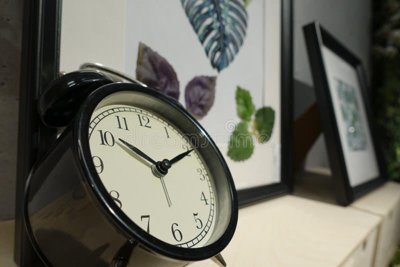 Le réveil de plan rapproché pour décorent autour des choses pour la conception de décoration intérieure sur le bureau en bois et  photos stock