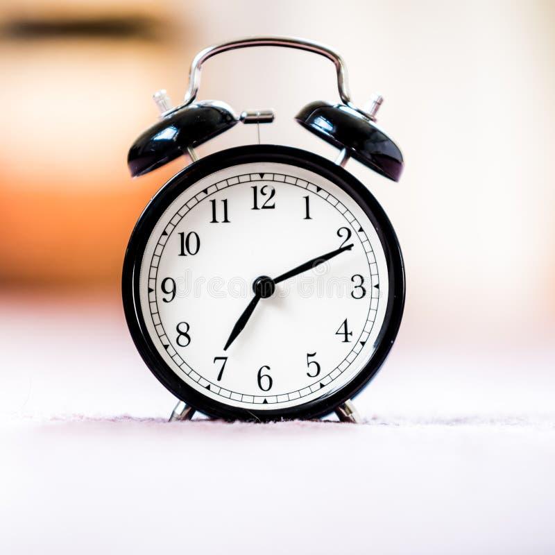 Le réveil noir de cru de la vie montre toujours le 7h du matin sur le fond lumineux de bokeh avec l'espace de copie Rétro horloge photo stock