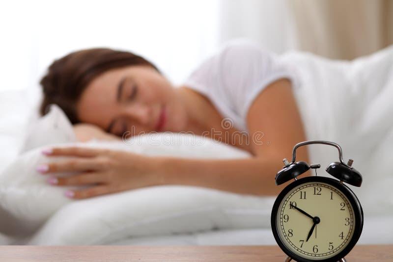 Le réveil se tenant sur la table de chevet a déjà sonné le début de la matinée pour réveiller la femme dans le lit dormant à l'ar photo libre de droits