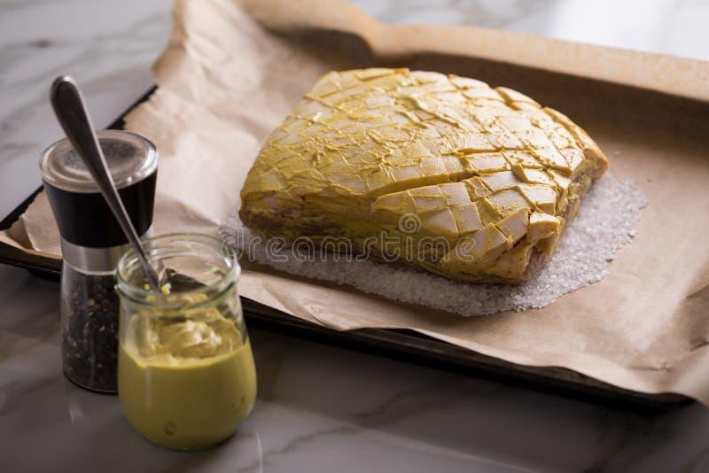 Le rôti de porc croustillant cru avec de la moutarde et le poivre marinent sur le plateau préparé et de cuisson de sel images libres de droits