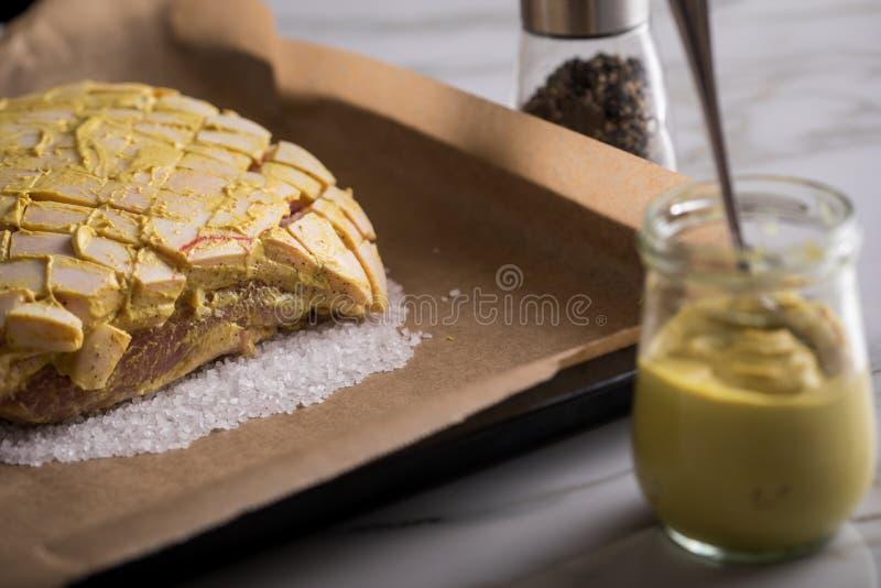 Le rôti de porc croustillant cru avec de la moutarde et le poivre marinent sur le plateau préparé et de cuisson de sel image libre de droits