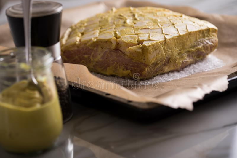 Le rôti de porc croustillant cru avec de la moutarde et le poivre marinent sur le plateau préparé et de cuisson de sel photographie stock libre de droits