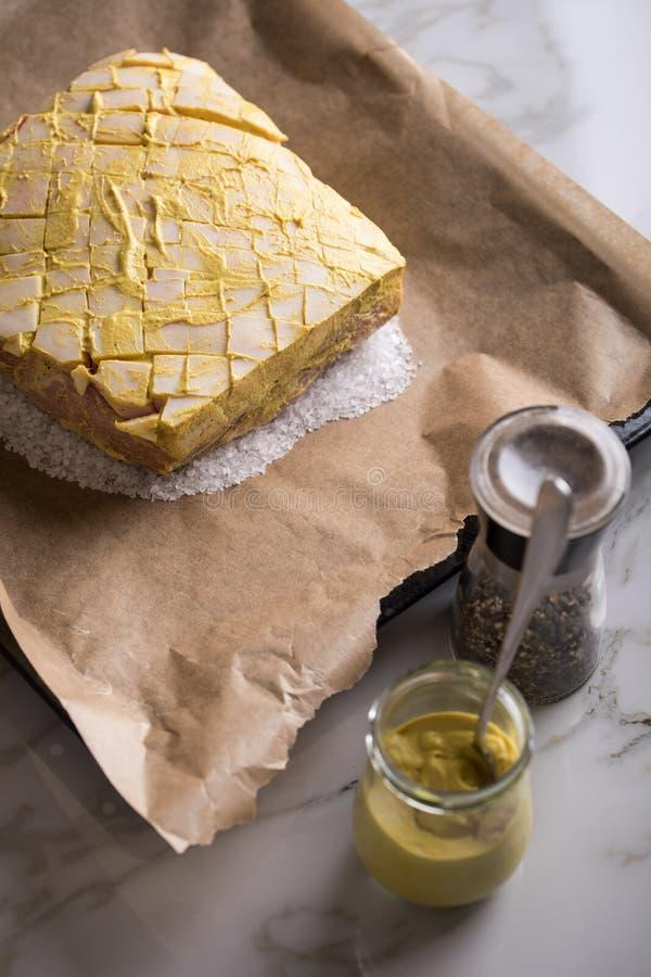 Le rôti de porc croustillant cru avec de la moutarde et le poivre marinent sur le plateau préparé et de cuisson de sel photos libres de droits