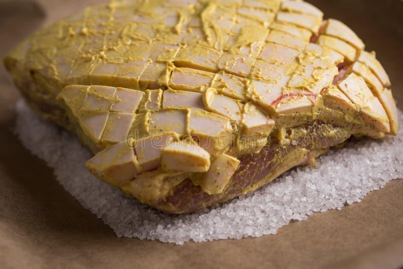 Le rôti de porc croustillant cru avec de la moutarde et le poivre marinent sur le plateau préparé et de cuisson de sel photos stock