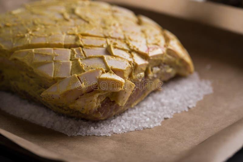 Le rôti de porc croustillant cru avec de la moutarde et le poivre marinent sur le plateau préparé et de cuisson de sel photographie stock