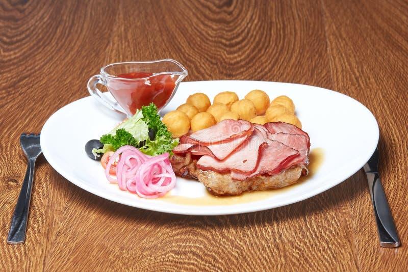 Le rôti de porc sur lequel se trouve la viande coupée en tranches en tranches minces, boules de fromage, anneaux d'oignon, olives image libre de droits