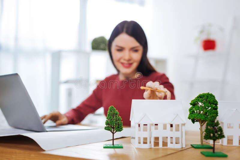 Le rörande miniatyrhus för kvinna, medan arbeta på hennes bärbar dator arkivbild