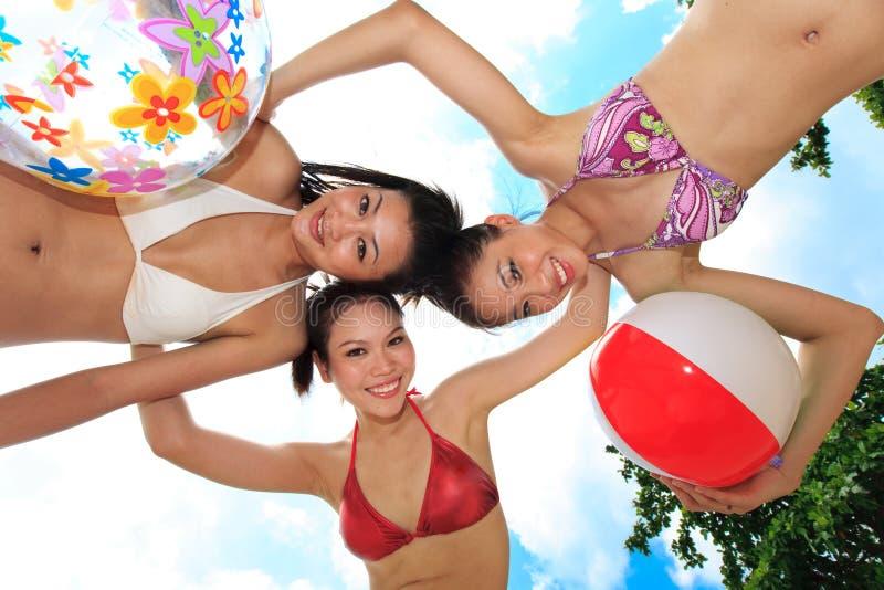 Le ragazze asiatiche hanno divertimento sotto il sole fotografie stock