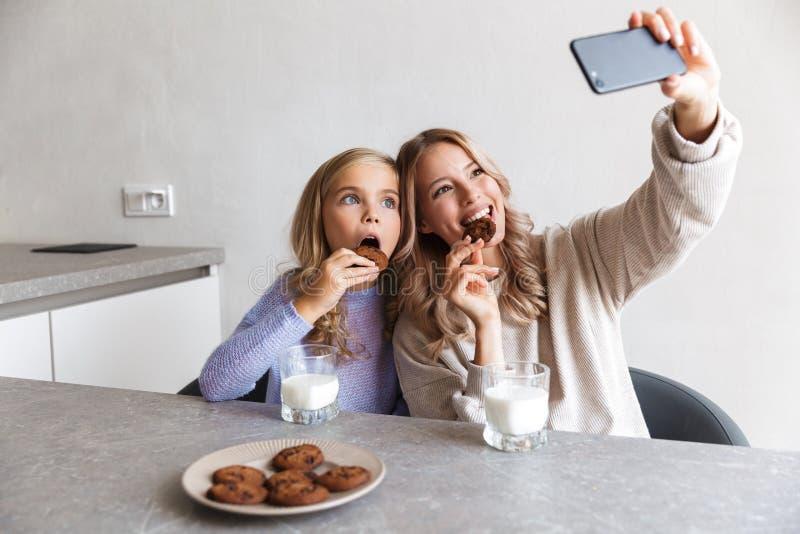 Le ragazze che felici le sorelle alla cucina all'interno mangiano hanno una prima colazione insieme prendono un selfie dal telefo immagine stock