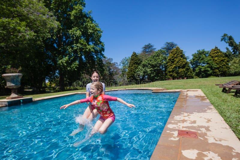 Le ragazze che saltano la piscina fotografia stock libera da diritti