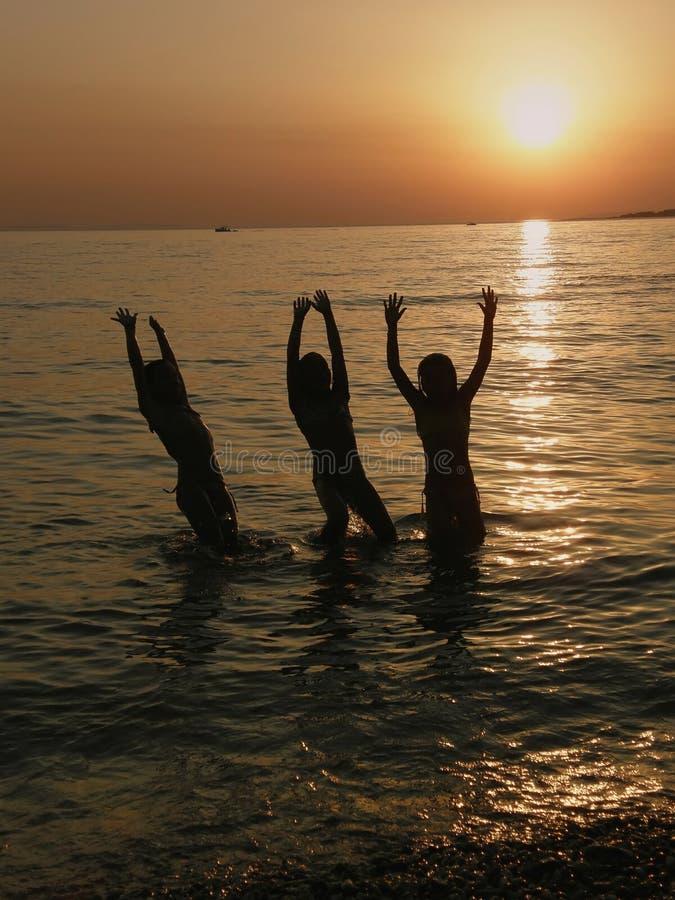 Le ragazze che saltano nel mare nel tramonto fotografia stock libera da diritti