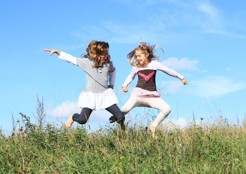 Le ragazze che saltano nell'erba immagini stock