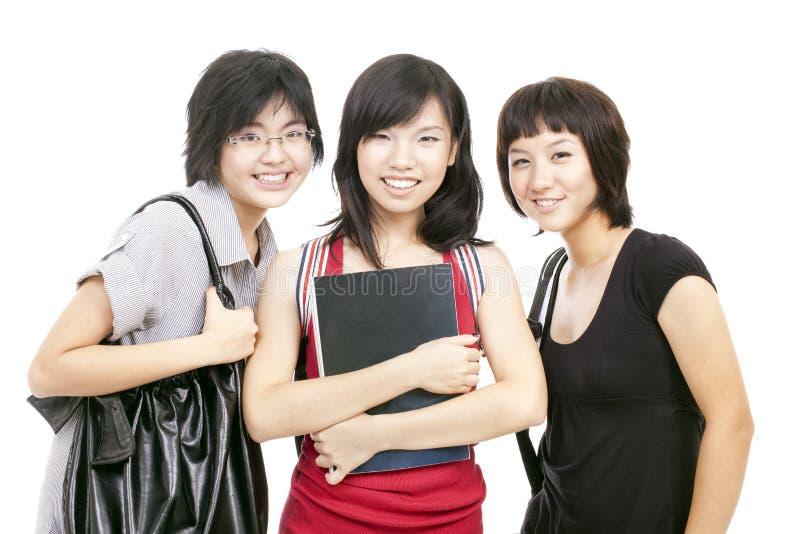 Le ragazze cinesi asiatiche dell'adolescente si raccolgono dopo il banco fotografie stock libere da diritti