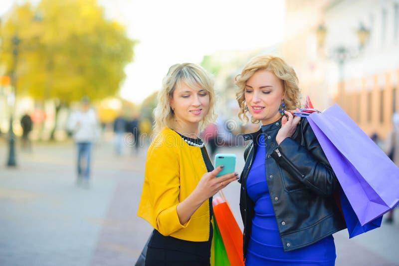Le ragazze con i pacchetti di acquisto sono sulla via e fanno un ordine dal telefono immagini stock