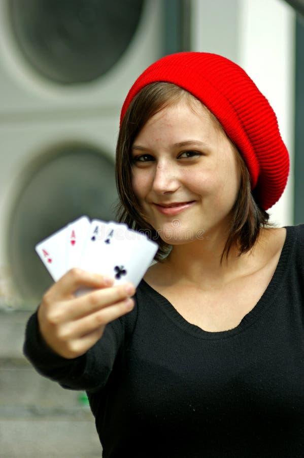 Le ragazze con la protezione rossa tiene quattro schede di gioco fotografie stock libere da diritti