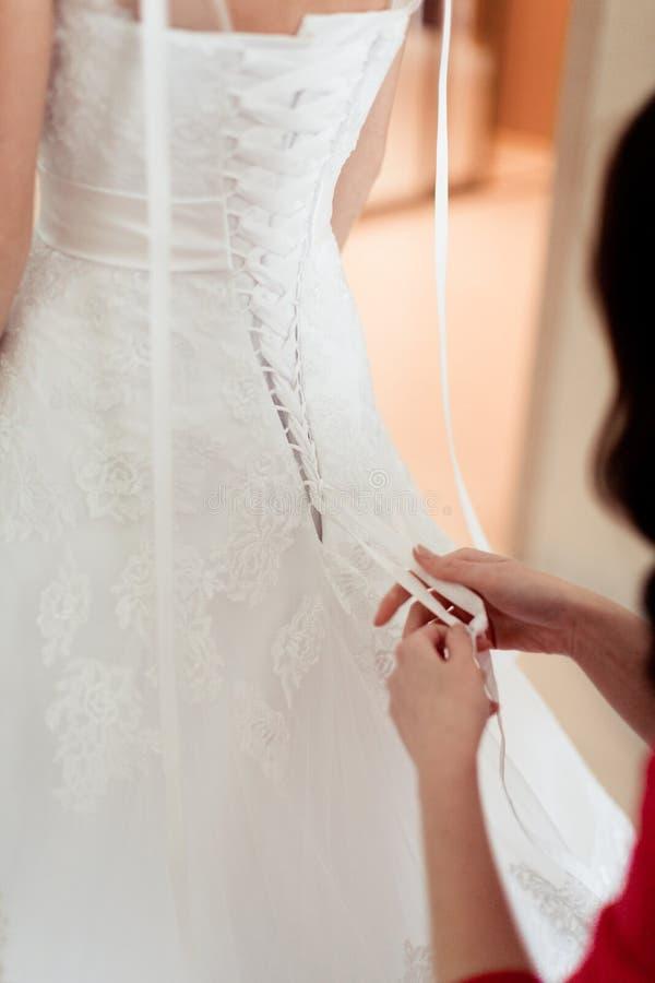 Le ragazze contribuiscono alla sposa ad abbottonare il vestito da sposa immagini stock libere da diritti