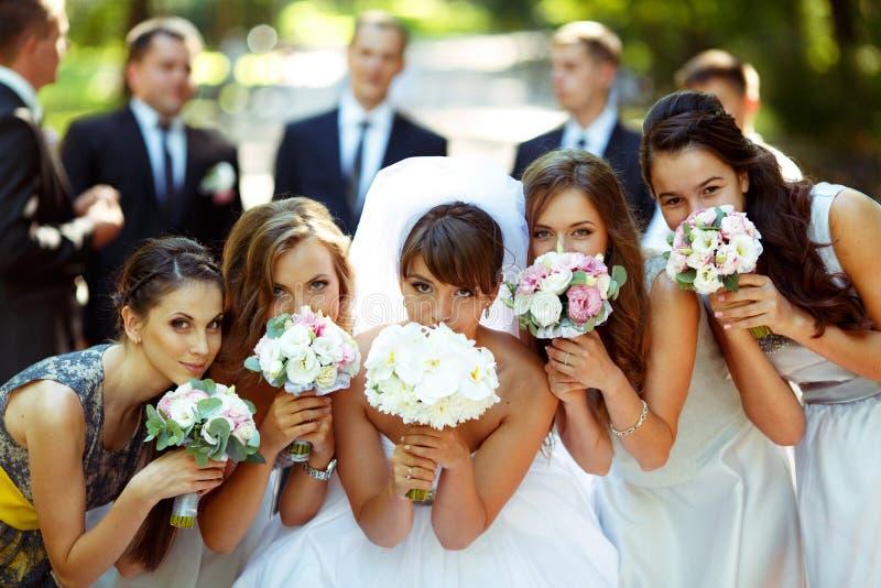 Le ragazze e la sposa posano con i mazzi di nozze mentre sposo e sposo fotografia stock libera da diritti