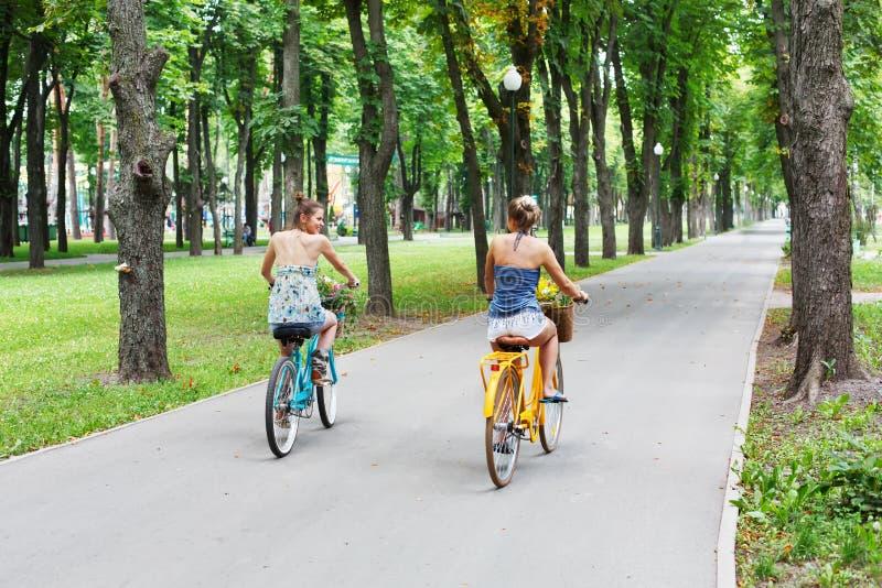 Le ragazze eleganti di boho felice guidano insieme sulle biciclette in parco fotografie stock libere da diritti