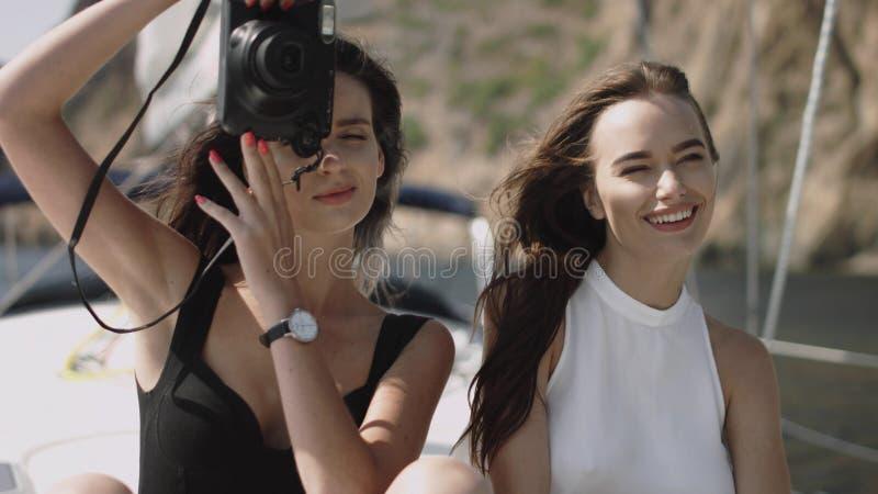 Le ragazze fanno le foto sull'yacht fotografia stock