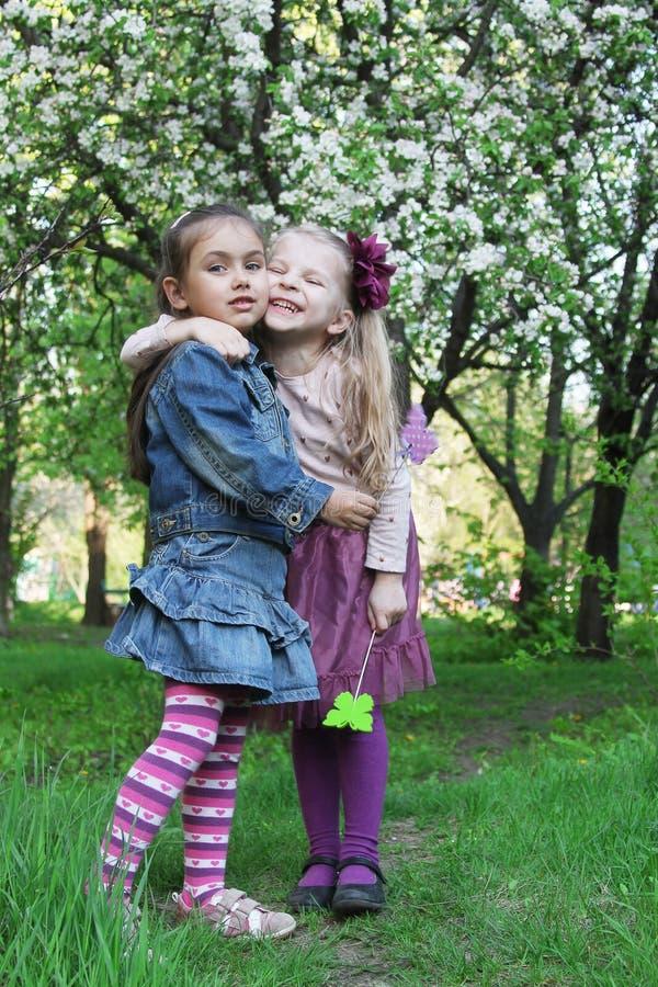 Le ragazze felici che giocano in primavera parcheggiano l'albero all'aperto immagini stock