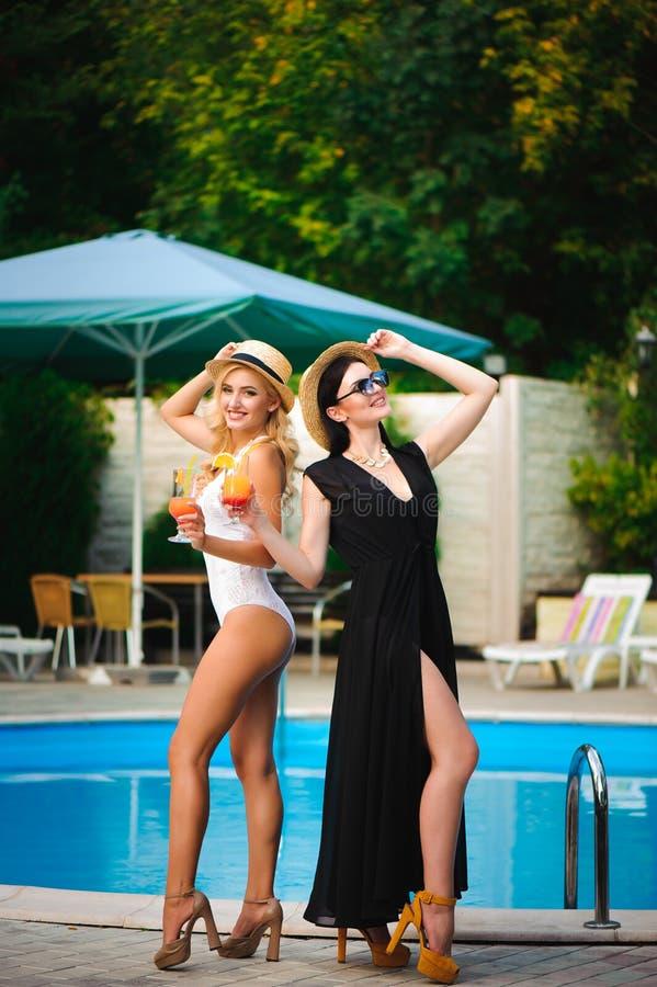 Le ragazze felici con le bevande sull'estate fanno festa vicino allo stagno immagine stock libera da diritti