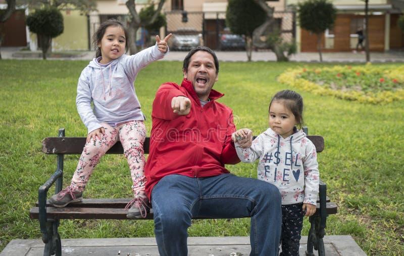 Le ragazze felici godono di buon tempo e della luce solare Bello stenditura dei bambini e gioco a vicenda ed il loro padre fotografie stock