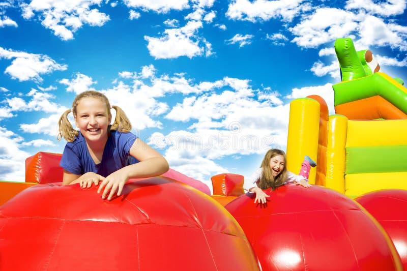 Le ragazze felici sopra gonfiano il castello immagine stock libera da diritti