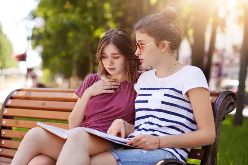 Le ragazze funloving allegre guardano attraverso l'emissione finale della rivista locale, discutono i nuovi eventi e la gente Gli fotografia stock libera da diritti