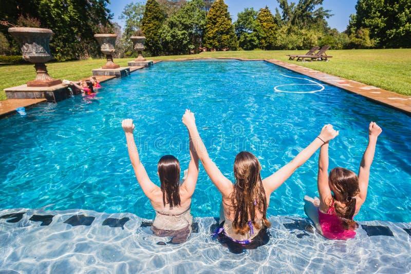 Le ragazze hanno messo la piscina a sedere fotografia stock