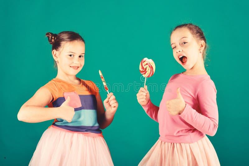 Le ragazze mangiano i grandi caramelli dolci variopinti Bambini con i fronti felici immagini stock libere da diritti