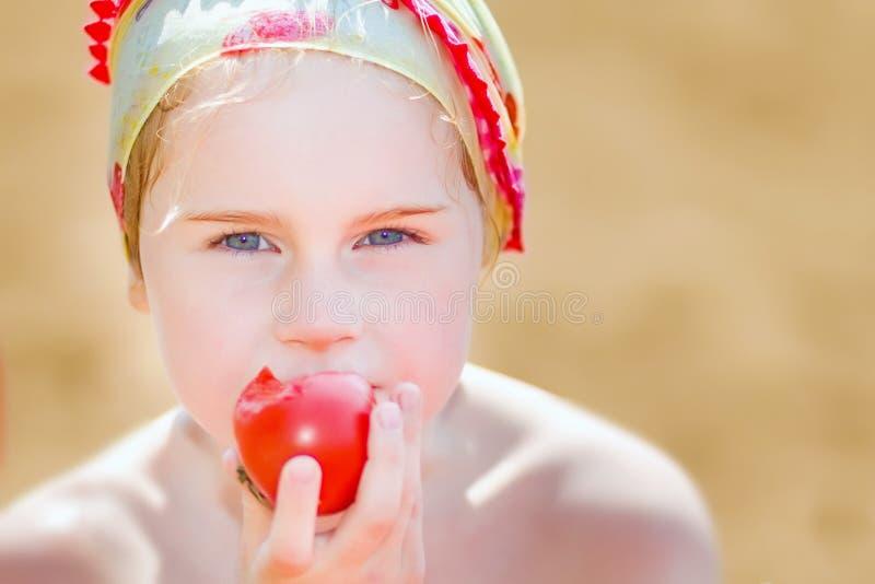 Le ragazze mangiano un pomodoro immagine stock libera da diritti