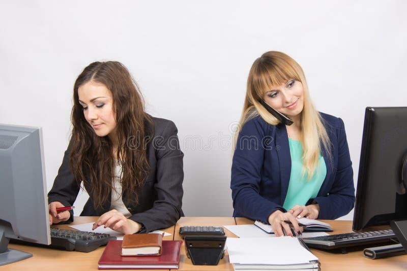 Le ragazze nell'ufficio, uno lavora nel computer, nell'altro sul telefono e nell'esame dello schermo immagine stock libera da diritti