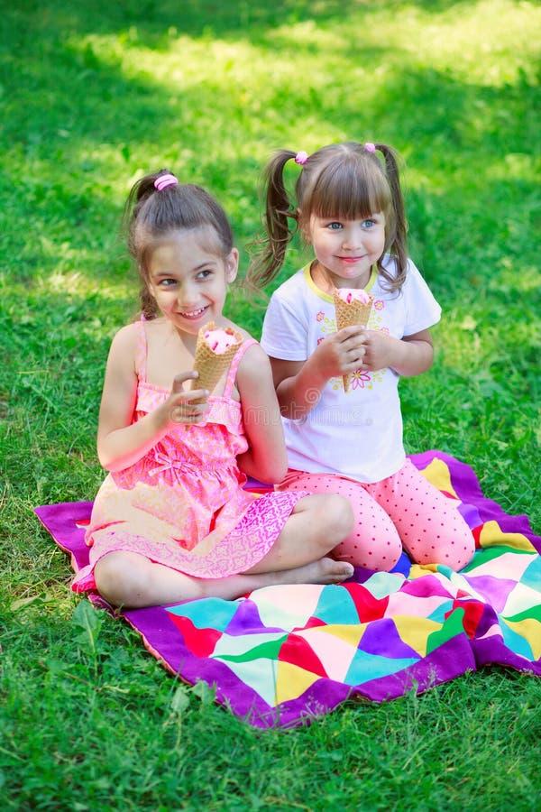 Le ragazze scherza gli amici delle sorelle che prendono in giro mangiando il gelato fotografie stock libere da diritti