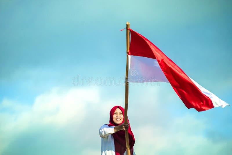 Le ragazze si vantano lo sbattimento della bandiera indonesiana con felicità con il backgorund del cielo blu immagini stock libere da diritti