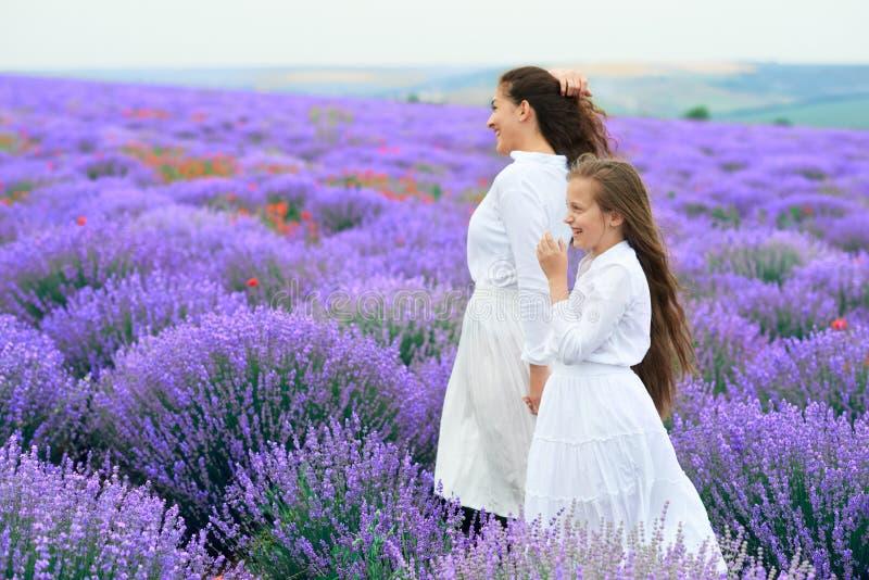 Le ragazze sono nel giacimento di fiore della lavanda, bello paesaggio dell'estate fotografia stock libera da diritti
