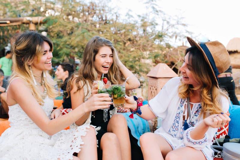 Le ragazze sorridenti allegre bevono per la riunione attesa da tempo, mentre spendono il tempo in caffè all'aperto nel giorno di  fotografia stock