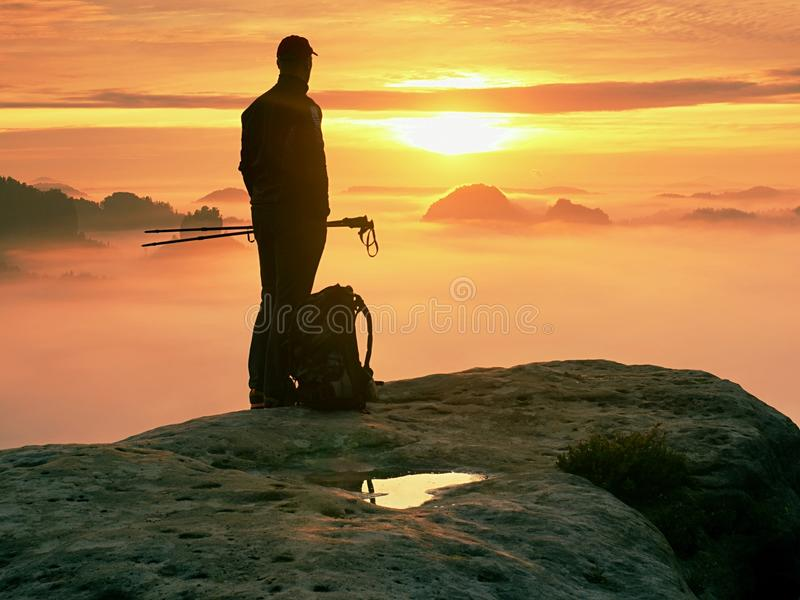 Le randonneur avec le sac à dos atteint le sommet de la crête de montagne Succès, liberté et bonheur en montagnes photographie stock libre de droits