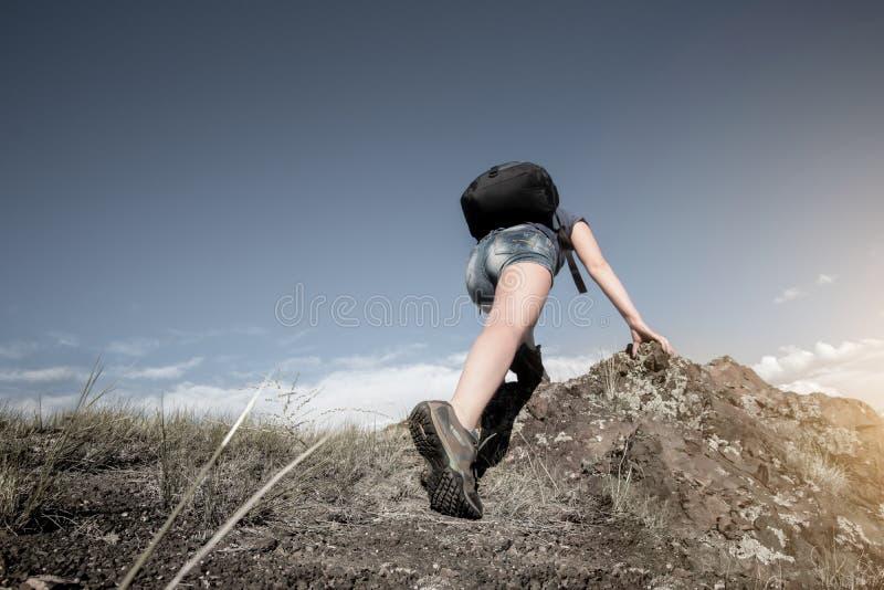 Le randonneur avec le sac à dos monte le terrain rocheux raide photographie stock libre de droits