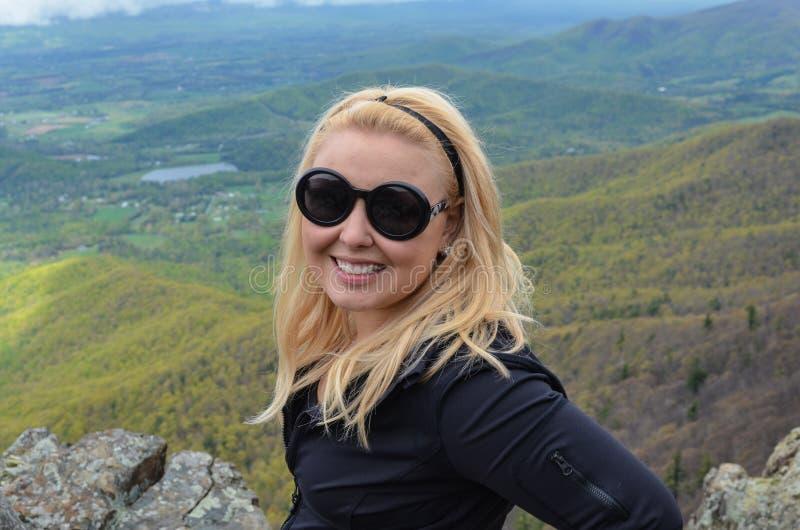 Le randonneur blond de femme féminine heureuse pose en haut du petit homme pierreux pour donner sur en parc national de Shenandoa photos stock