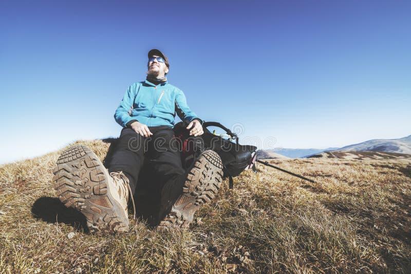 Le randonneur dans des chaussures de trekking se repose sur le dessus d'une montagne image libre de droits