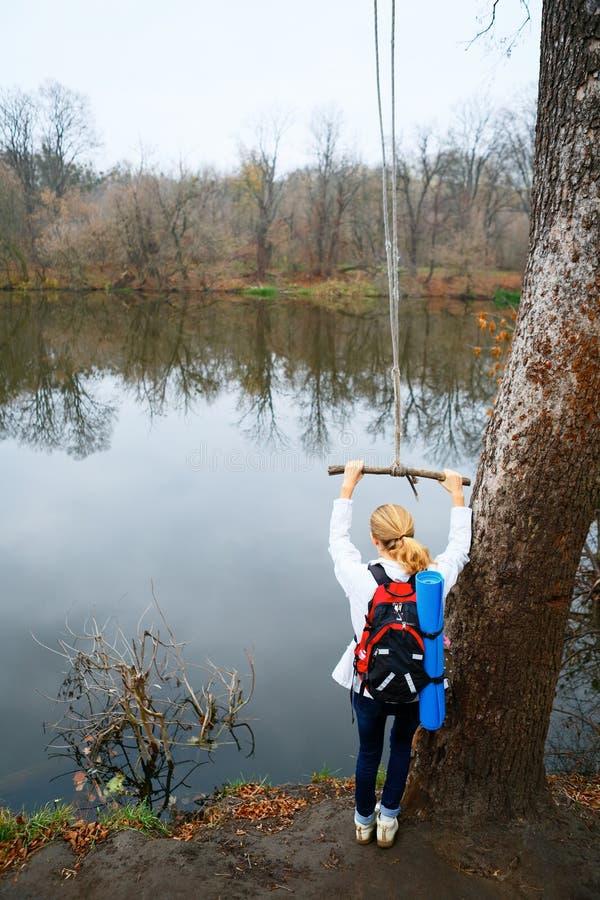 Le randonneur de femme avec le bungee dans les mains s'approchent de la rivière d'automne photos stock