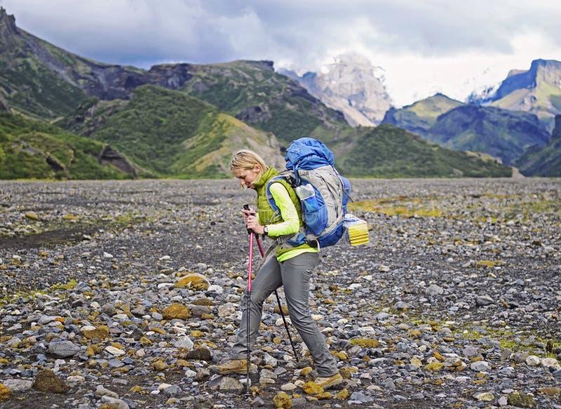 Le randonneur de femme avec le sac à dos marchant vers le haut de la traînée avec de belles crêtes de montagne regardent le paysa photographie stock