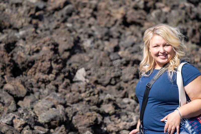 Le randonneur de femme pose sur la traînée à Lava Butte sur la traînée des terres fondues en monument volcanique national de Newb photos stock
