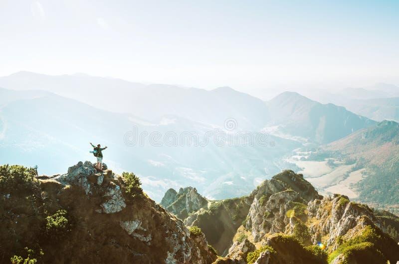 Le randonneur de montagne avec la figurine minuscule de sac ? dos se tient sur la cr?te de montagne avec le beau panorama image stock