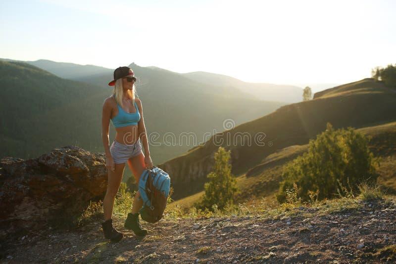 Le randonneur de touristes de montagne de femme avec le sac à dos se tient sur des montagnes photographie stock libre de droits