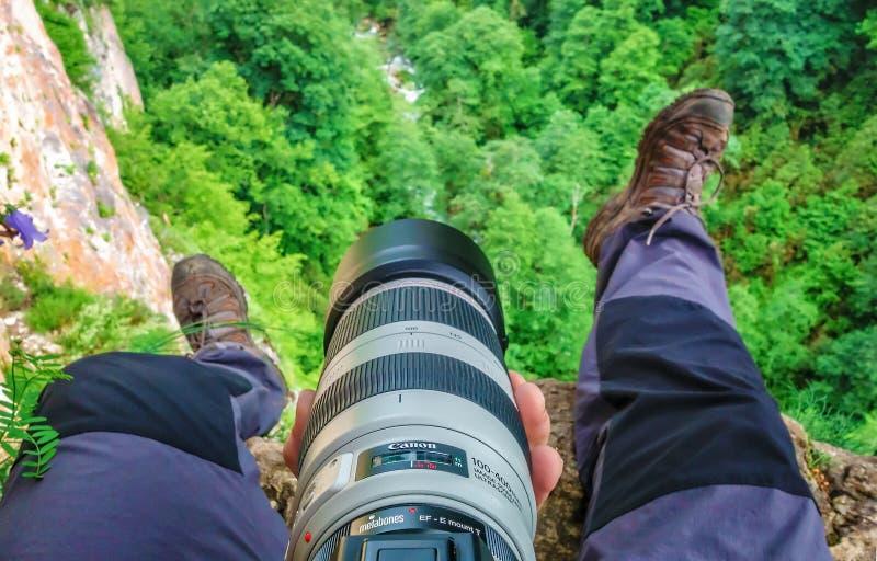 Le randonneur et le photographe d'homme au travail s'assied sur le bord de la roche de montagne en montagnes de Caucase photographie stock libre de droits